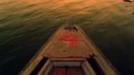 Boat point of view tilt up from bow of boat to wide shot Ganges River with ghat and buildings on shore /Varanasi, India