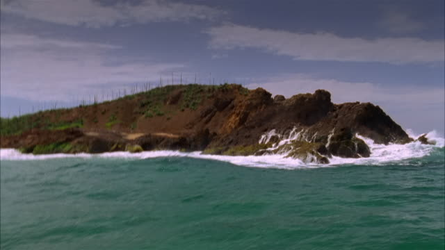 Boat point of view wide shot waves splashing onto beach and crashing against rocky coastline / Costa Careyes, Mexico