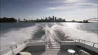 A boat speeds across Sydney Harbor and away from the Sydney skyline.