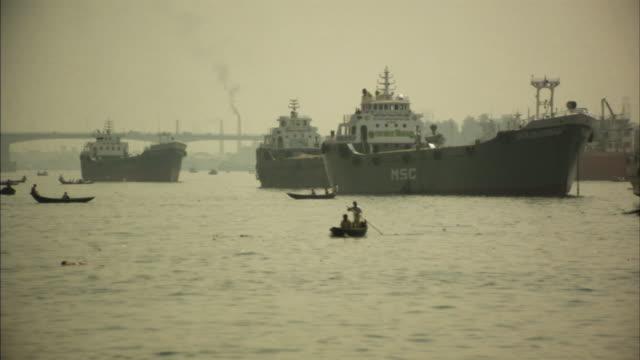 WS, Boat traffic on Buriganga river, smoke stacks in background, Dhaka, Bangladesh