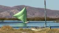Boat with bright green sail on Lake Titicaca, with reeds and mountains in b/g, another boat in f/g, near Tiwanaku Tiahuanaco/Tiahuanacu, Bolivia