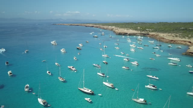 AERIAL Boats anchored in bay with clear, blue water
