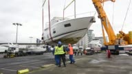 Boats are lifted onto trailers outside Excel London so they can be displayed at the London Boat Show at ExCel on December 18 2015 in London England...