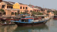 Boats bob at anchor in the harbor of the ancient city of Hoi An Vietnam