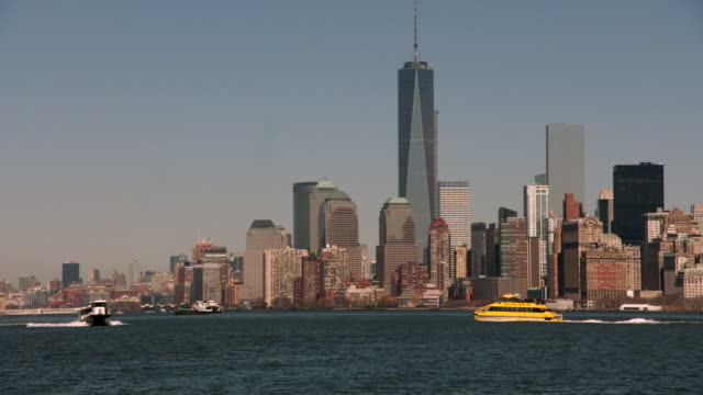 TS Boats move through New York Harbor with the skyline of Lower Manhattan in the background / New York, United States