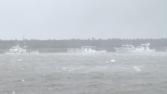 Boats tied securely in small fishing port as typhoon Noru hits Japan