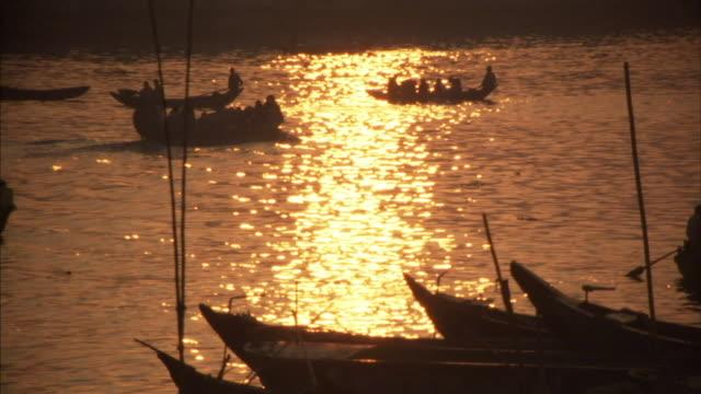 MS, Boats transporting people through Buriganga river at sunset, Dhaka, Bangladesh