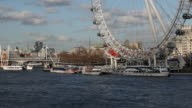 Boats travel along the river Thames in front of the London Eye Ferris wheel on February 21 2014 in London England