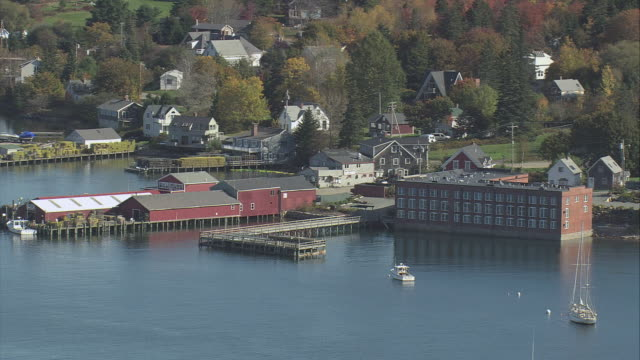 AERIAL Boat-sheds at waterfront, open docks, anchored schooner, motorboat crossing the harbor, and town with autumn foliage beyond / Bass Harbor, Maine, United States
