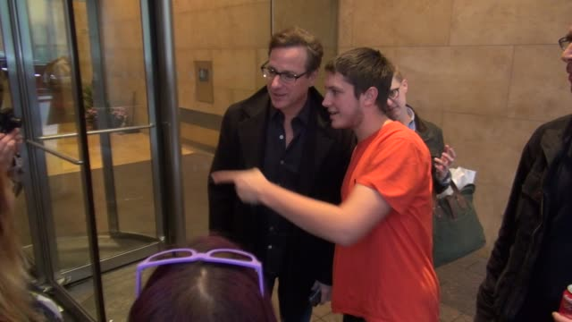 Bob Saget exits SiriusXM Satellite Radio poses with signs for fans before getting into his car in Celebrity Sightings in New York