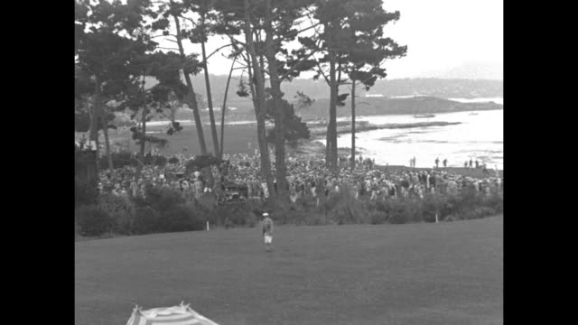 CU Bobby Jones / VS man writes numbers on chalk scoreboard / tilt down tee off near water / MS gallery follows players over course ocean in bkgd /...