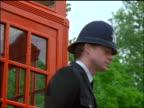 PORTRAIT bobby turning towards camera + nodding outdoors / telephone booth in background / London