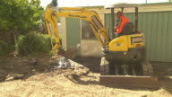 bobcat with bucket load of dirt and rubble in backyard pan to 'New Holland' caterpillar track backhoe digger / bobcat scoops up pile of rubble and...
