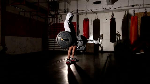 Bodybuilder met de kap Gewichtheffen in de sportschool