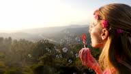 Boho beautiful girl blowing bubbles