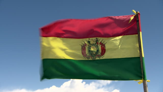 CU of Bolivian national flag, La Tricolor, in the wind, blue sky with clouds, shot on Lake Titicaca, Bolivia