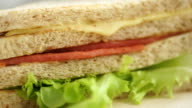 Bologna and cheese whole wheat sandwich on wooden board.