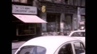 Bomb damaged and dilapidated buildings at the border of East and West Berlin pan to Checkpoint Charlie / Volkswagen entering the checkpoint / Men in...