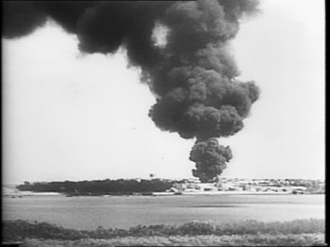 Bombed church in Darwin Australia / Australia citizens gathered on street corner / montage of destroyed buildings / Japanese warplanes overhead /...