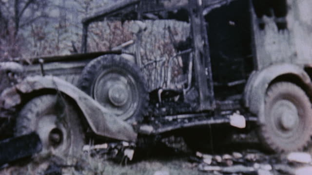 Bombed out vehicles in fields and US Army soldier examining rocket ammunition spilled from crates and wrecked truck / Germany