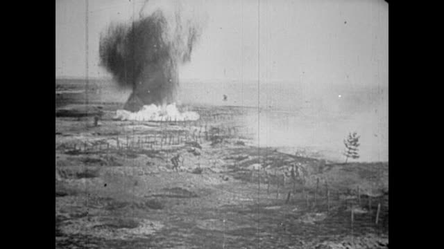 Bombs exploding over farm landscape / German soldiers in trenches running out into the fields / soldiers run from trench to trench as bombs get...