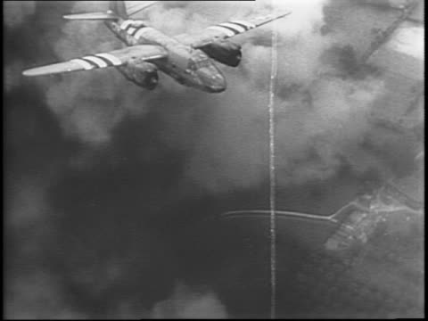Bombs falling / airtoair three B17s release bombs / aerial through smoke clouds bombs drop and explode / C47 transport plane flies into frame