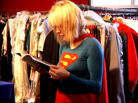 Bonhams auction of movie costumes INT Model wearing Supergirl costume looking thru catalogue