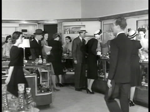 Bonwit Teller department store New Yorkers pedestrians INT Department store shoppers perfume MS Woman man smelling perfume CU Perfumes 'Caron' CU...