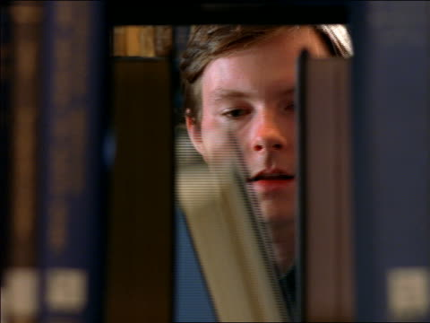 Books in bookshelf removed REVEAL male student examining books / Boston, MA