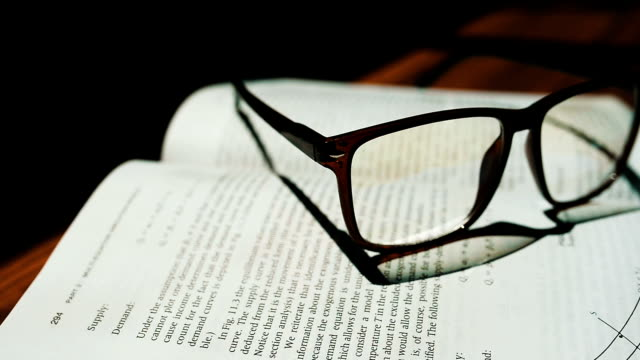 books on desktop with glasses on open pages