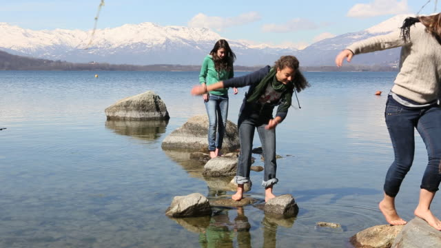 Boom as teen  girls follow stepping stones from mountain lake