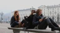 Boom of 3 teenage girls using ipad, cell phone in piazza