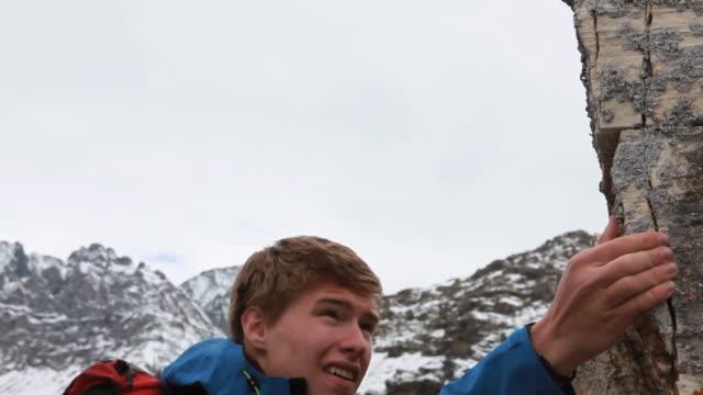 Boom shot of teen climbing steep ridge, stormy day