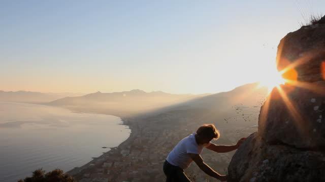 Boom upwards as man climbs cliff above sea, sunset