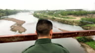 A US Border Patrol agent scans the USMexico border while on a bluff overlooking the Rio Grande on March 13 2017 in Roma Texas The Border Patrol has...