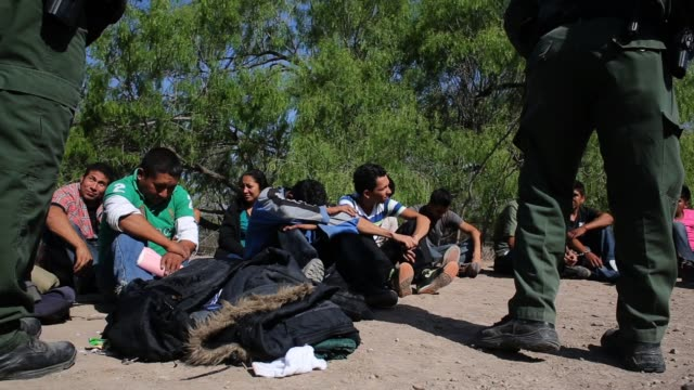 US Border Patrol agents detain a group of 16 immigrants from Mexico and El Salvador who had just crossed the Rio Grande River from Mexico into Texas...