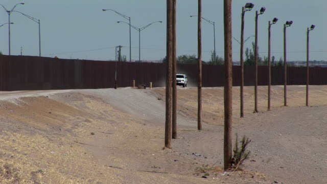 TS WS PAN Border Patrol vehicle driving next to new high security border barrier, El Paso, Texas, USA