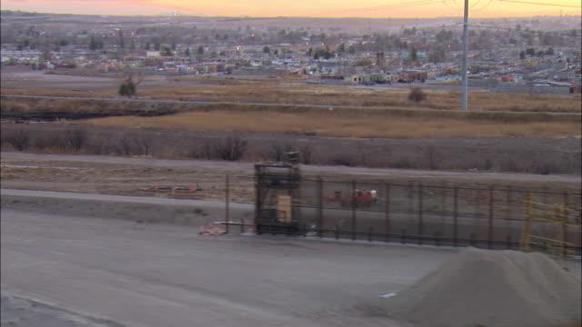 LOW AERIAL 'Border wall' along US-Mexican border at El Paso under construction and view of Juarez, Mexico, Texas, USA