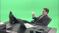 MS, Bored businessman throwing paper plane at desk in studio