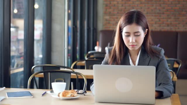 Gelangweilte junge Geschäftsfrau im Café arbeiten.