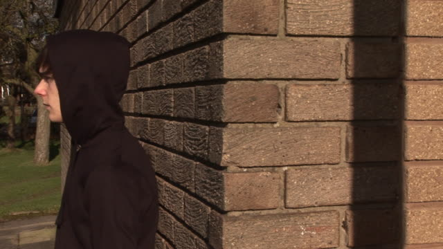 Bored young man / hoody, leaning against brick wall