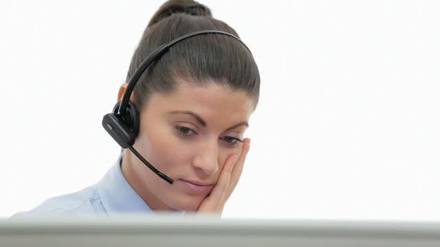 De klantenservice van verveeld jonge vrouw achter de computer praten over de headset.