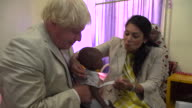 Boris Johnson and Priti Patel playing with a child on a visit to a hospital in Nigeria