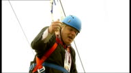 Boris Johnson gets stuck on zip wire ENGLAND London Victoria Park EXT Boris Johnson along zipwire waving two Union Jack flags Johnson dangling from...