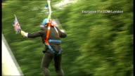 Boris Johnson gets stuck on zip wire ITV ENGLAND London Victoria Park EXT Boris Johnson along zipwire waving two Union Jack flags GVs Johnson...
