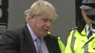 Boris Johnson Mayor of London joins police to promote cycling safety Shows Boris Johnson Lord Mayor London crossing road holding bicycle accompanied...
