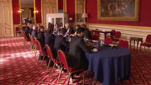 BorisJohnson and Rex Tillerson attend talks at Lancaster House ENGLAND London INT Boris Johnson and Rex Tillerson sitting at meeting table with others