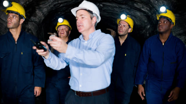 Boss showing miners what to look for