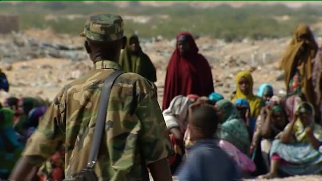 Bossaso Soldier with group of women and children in background Queue of women and children Girl wearing bright headscarf View across rubbish on...