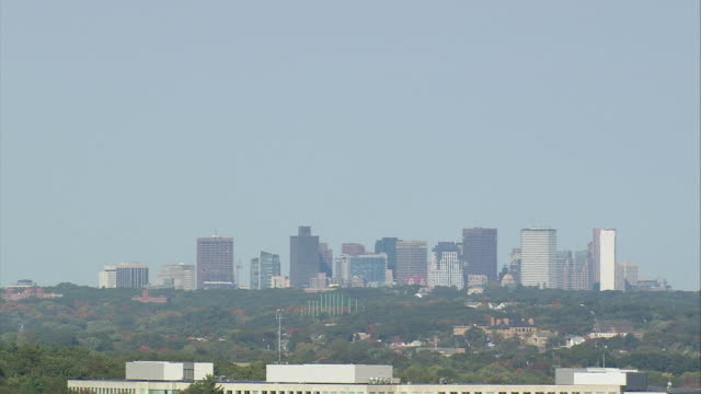 AERIAL Boston city skyline beyond commercial building / Quincy, Massachusetts, United States